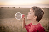 boy blowing up the soap bubbles on sepia toned landscape