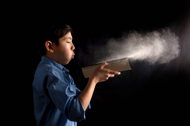 Boy blows dust off book. stock photo