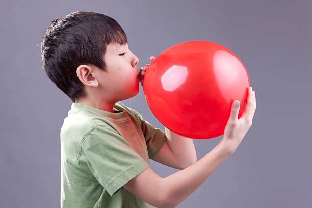 Boy blows up balloon. stock photo