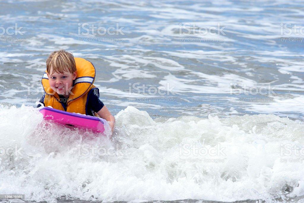 Boy boarding in surf stock photo