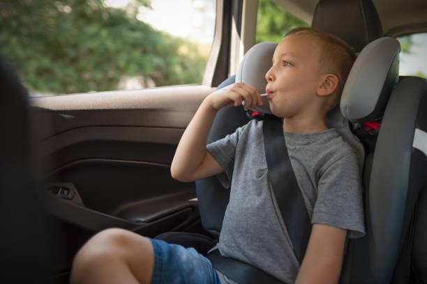 pojke som spände till bilbarnstol - remmar godis bildbanksfoton och bilder