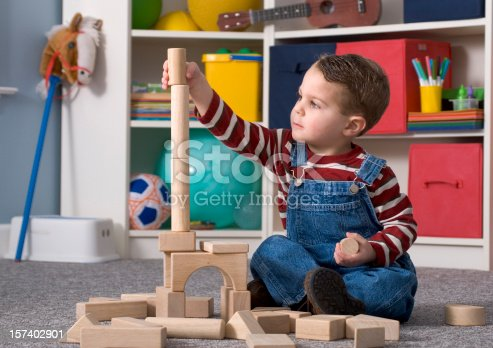 Shown here is a two-year-old boy happily playing with and looking at a tall stack of wooden toy blocks.  No visible logos. All toys are generic & non-branded.