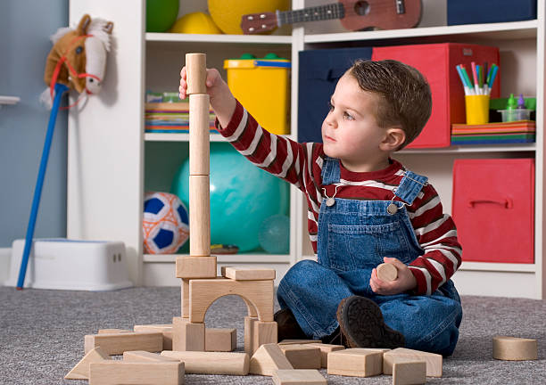 Boy Building With / Looking At Tall Wooden Toy Blocks Horizontal stock photo