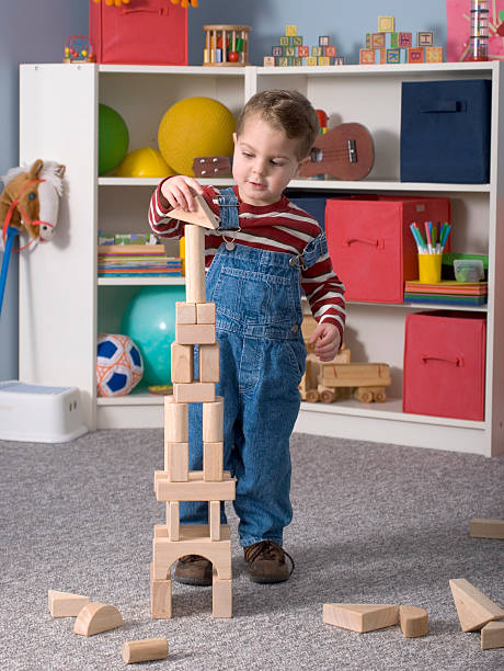 Boy Building With / Looking At Wooden Toy Blocks, Close, Vertical stock photo