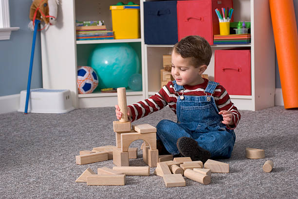 Boy Building With / Looking At Wooden Toy Blocks, Horizontal stock photo