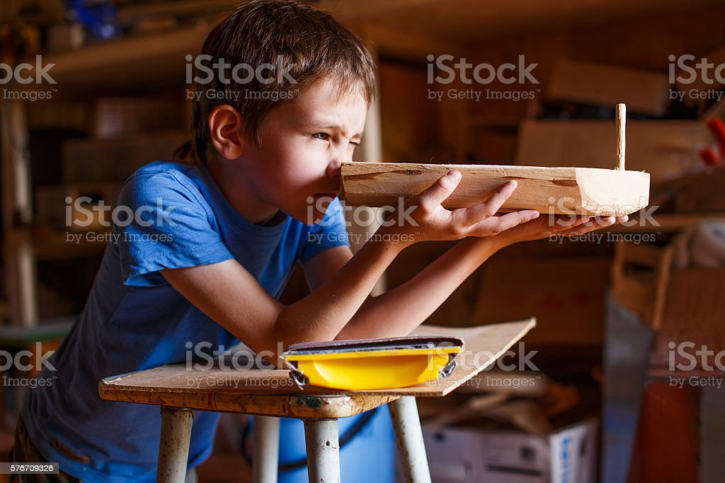 boy builds a toy ship of wood stock photo