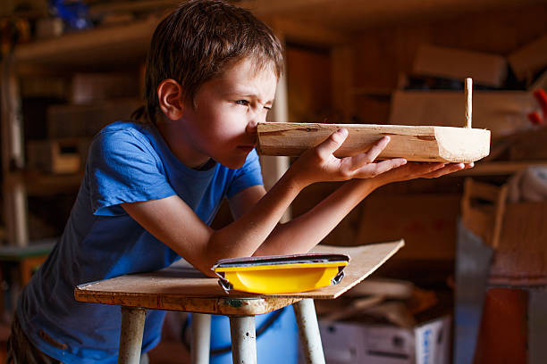 boy builds a toy ship of wood child in the workshop makes crafts. toy boat of wood carving craft activity stock pictures, royalty-free photos & images