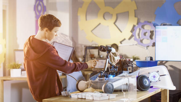 Boy Builds Fully Functional Robot with Bright LED Lights and Programs it with Laptop for His School Robotics Club Project. stock photo