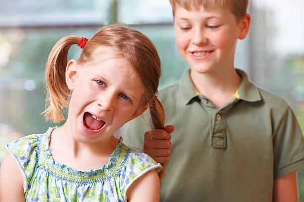 menino intimidar menina puxando o cabelo - puxar cabelos imagens e fotografias de stock