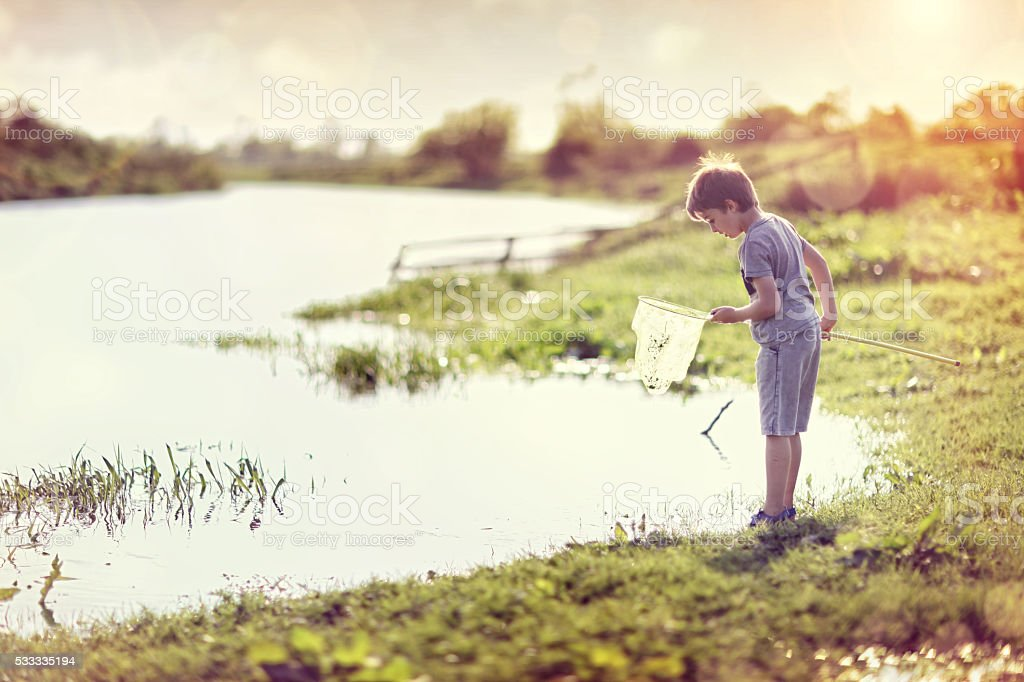 Boy by a river with a fishing net in summer sun stock photo