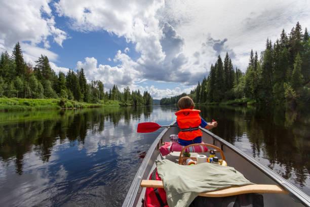 canot de garçon pagayer sur la rivière dans le nord de la suède - nuage 6 photos et images de collection