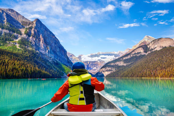 Boy Canoeing on Lake Louise in Banff National Park Canada Teen boy canoeing on Lake Louise in Banff National Park of the Canadian Rockies with its glacier-fed turquoise lakes and Mount Victoria Glacier in the background. mt victoria canadian rockies stock pictures, royalty-free photos & images