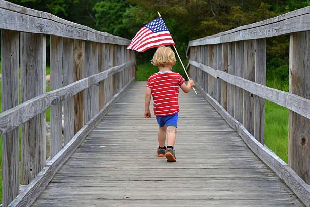 boy carrying american flag over bridge - independence day stock photos and pictures