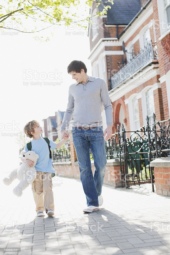Boy carrying teddy bear and holding fathers hand on sidewalk royalty-free stock photo
