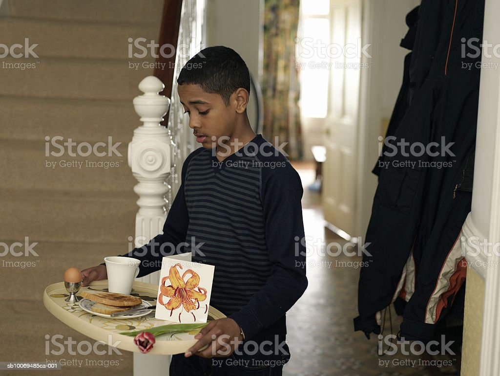 Boy (12-13) carrying tray with breakfast and flower through hallway royalty free stockfoto
