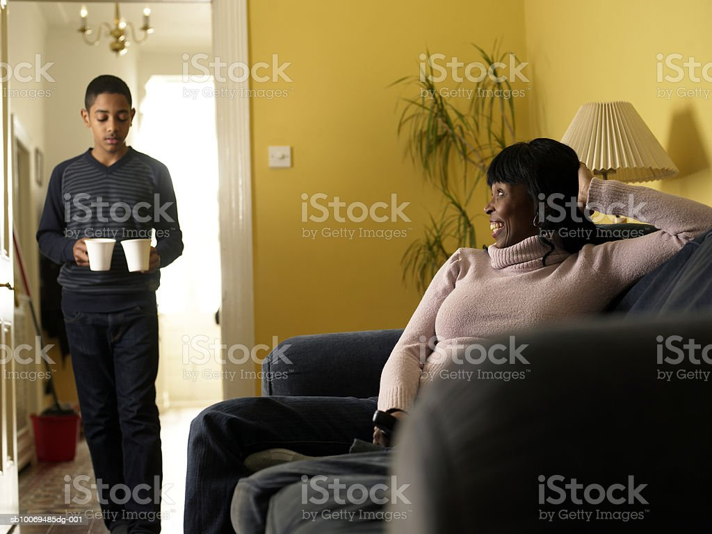 Boy (12-13) carrying two mugs, mother sitting on sofa royalty-free stock photo