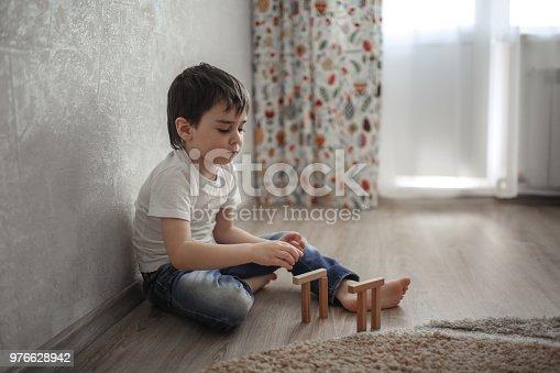 470874196istockphoto Boy Caucasian brunette sad and serious plays 976628942