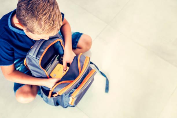 Junge prüft die SCHULRUCKSACK – Foto