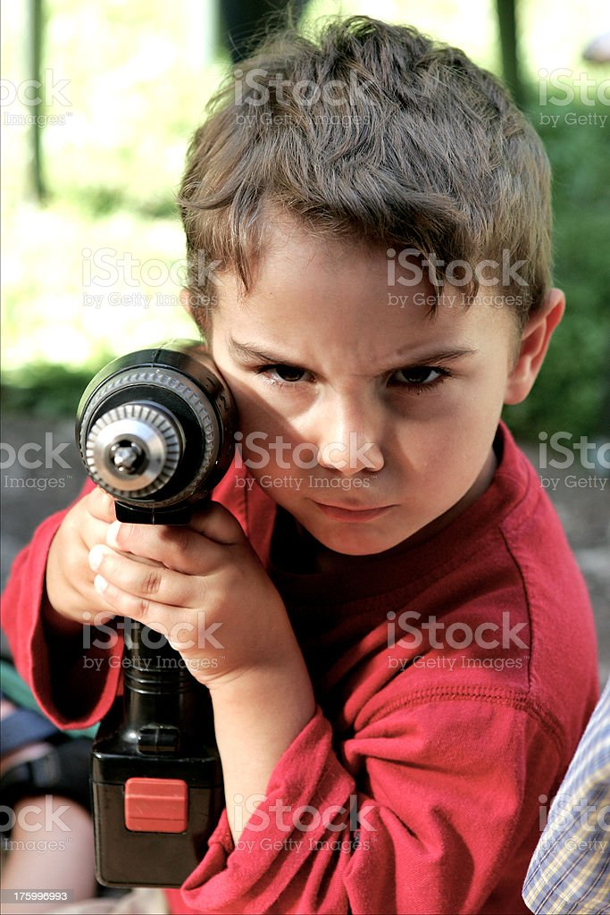 Boy child aims with drill royalty-free stock photo