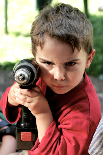 Boy child aims with drill