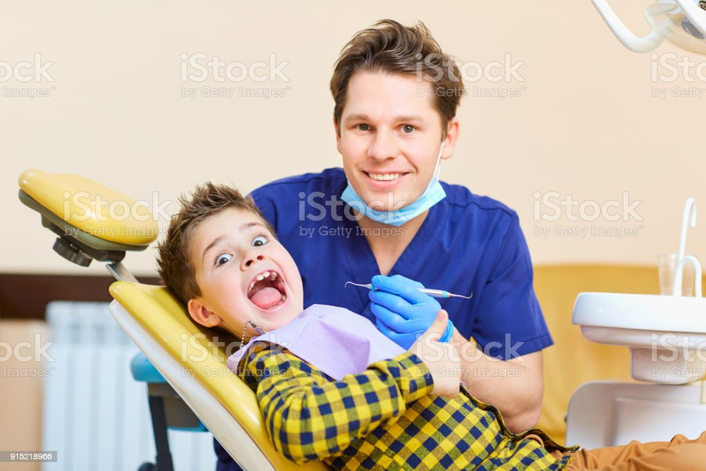 A boy child and a dentist man raised their thumbs stock photo