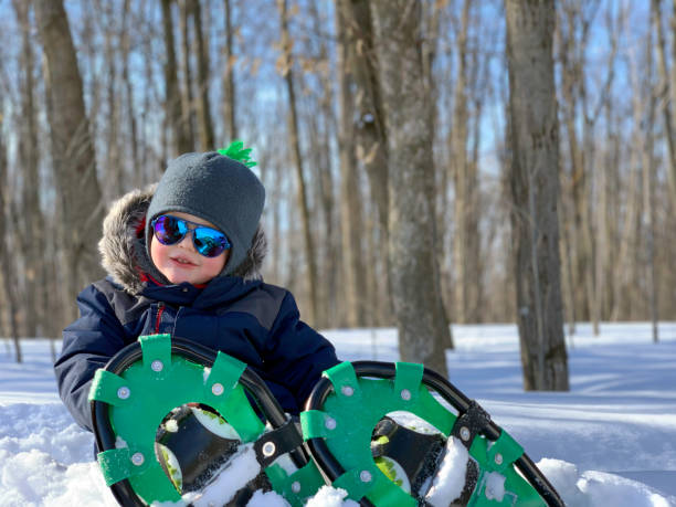 Boy Child Snowshoeing Outdoors in Winter After Snowstorm stock photo
