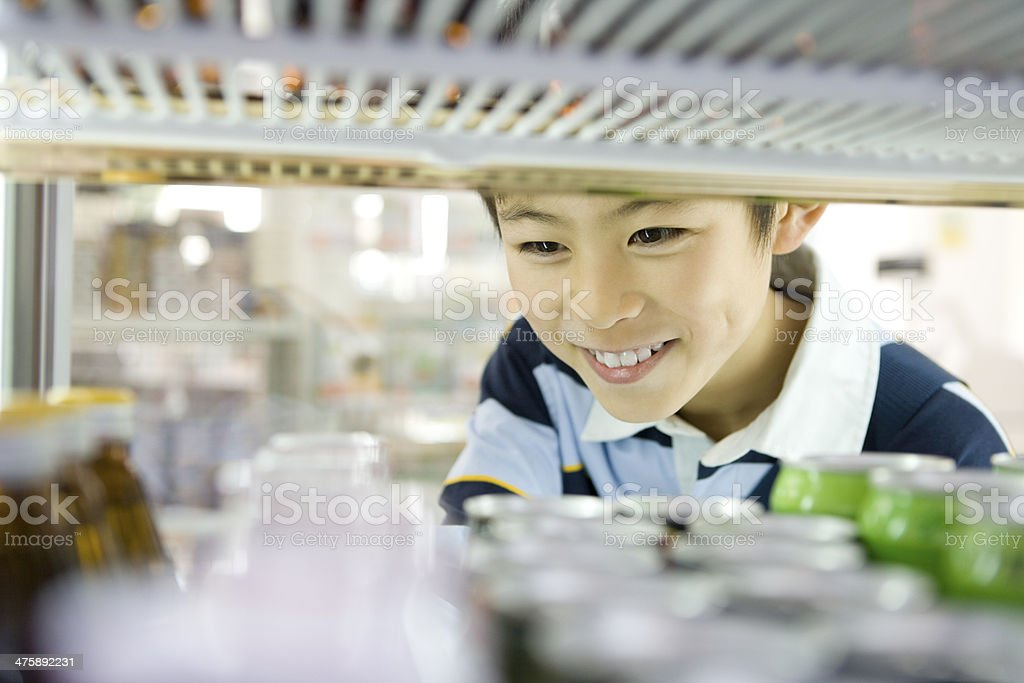 Boy choosing drink at convenience store stock photo