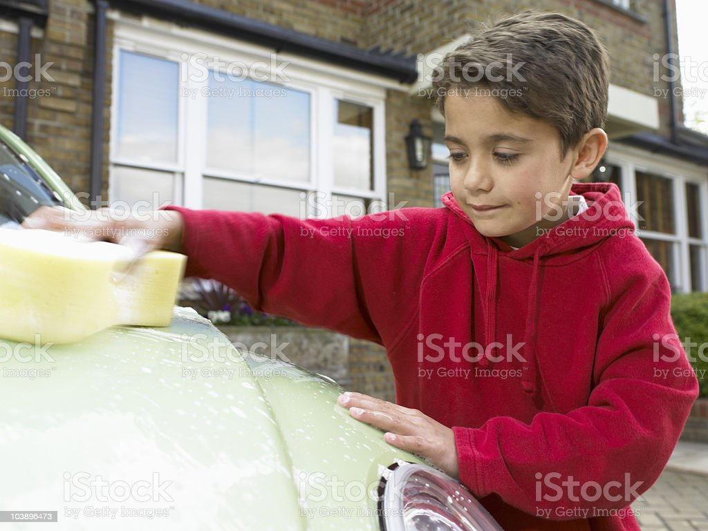 Boy cleaning car outdoors royalty-free stock photo