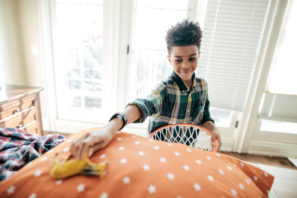 Boy cleaning his room A boy is cleaning his bedroom. kids cleaning up toys stock pictures, royalty-free photos & images