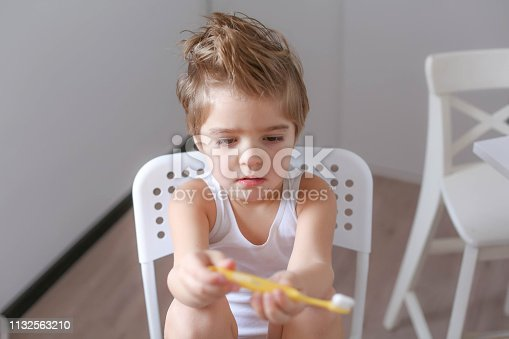 948443044istockphoto Boy cleans his teeth in the morning and plays with a toothbrush 1132563210