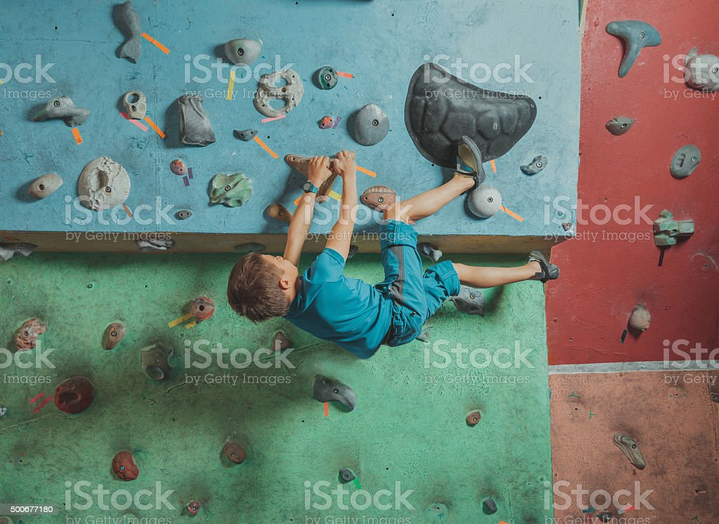 Boy climbing in gym stock photo
