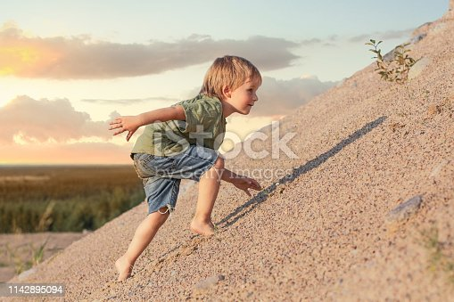 Boy Climbing On Mountain. Summer day and sand dune.