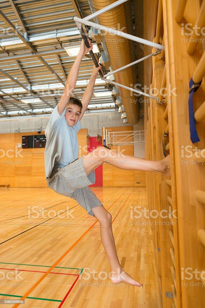 Boy Climbing/Exercising on Wall Bars in School Gymnasium, Europe stock photo