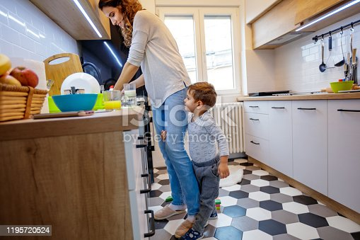 Cute 2,5 year old child seeking attention from his mother, clinging to her leg while she's trying to wash dishes
