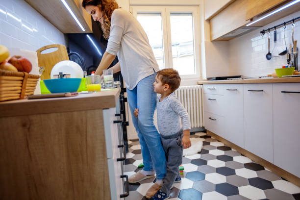 Boy clinging to his mother leg Cute 2,5 year old child seeking attention from his mother, clinging to her leg while she's trying to wash dishes perching stock pictures, royalty-free photos & images
