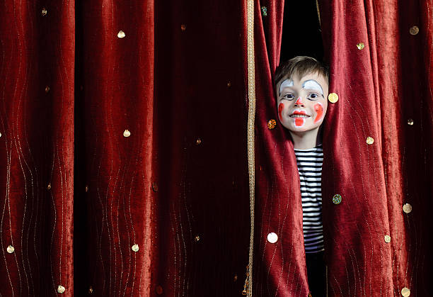Boy Clown Peering Through Stage Curtains Young Boy Wearing Clown Make Up Peering Out Through Opening in Red Stage Curtains theatrical performance stock pictures, royalty-free photos & images