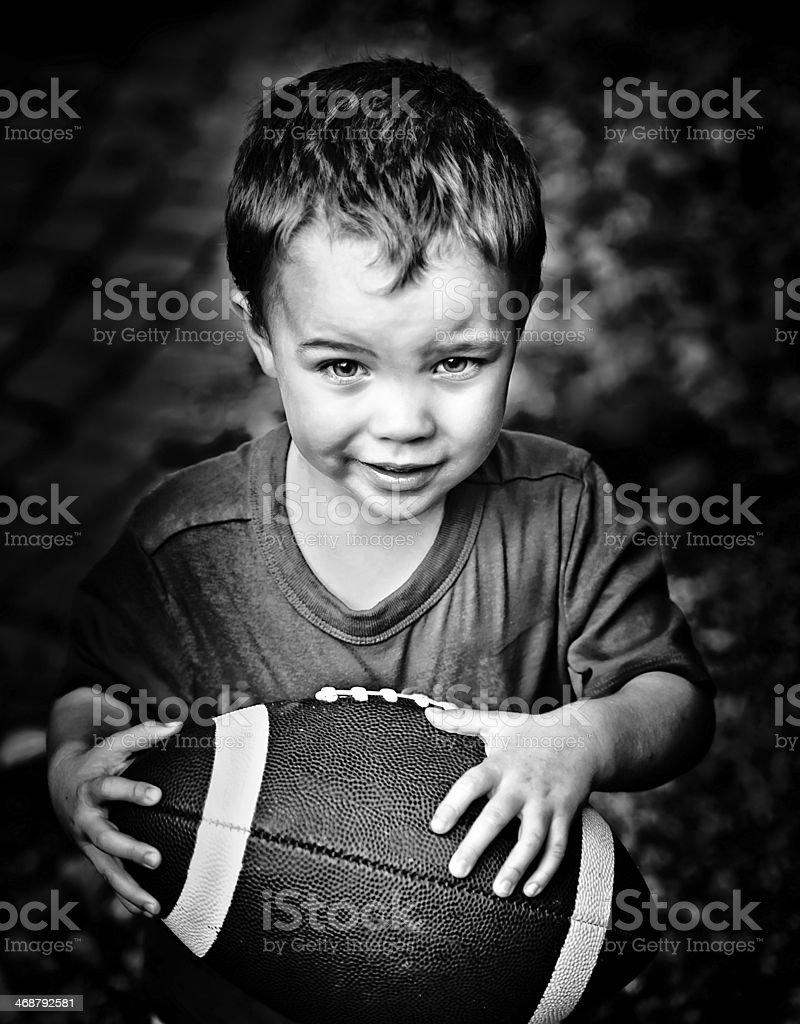 Boy Clutching American Football B&W stock photo
