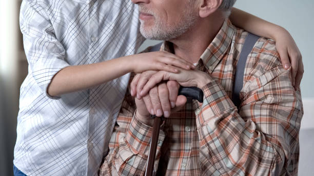 Boy consoling old lonely man, embracing him, charity program in nursing home Boy consoling old lonely man, embracing him, charity program in nursing home sentimentality stock pictures, royalty-free photos & images