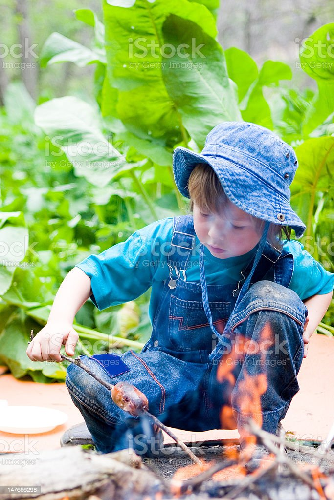 Boy cooking sausage by bonfire in hike (series children) stock photo