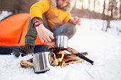Boy cooking tea on a camp fire.