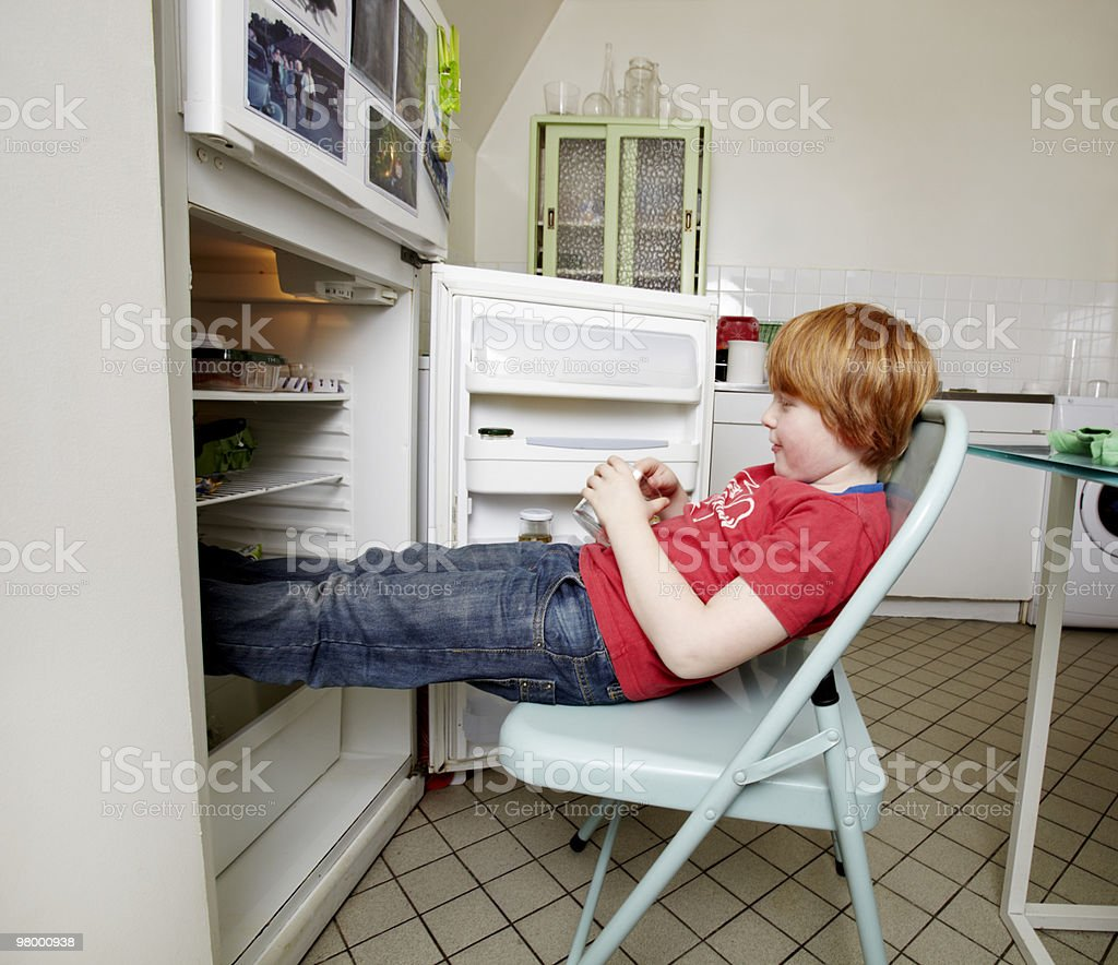boy cooling feet in refrigirator royalty-free stock photo