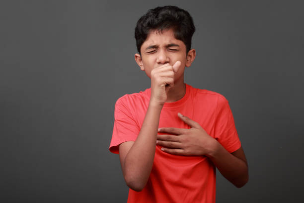 boy coughs by closing his mouth by hands - tossire foto e immagini stock