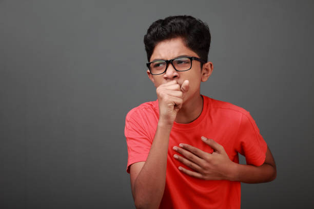 Boy coughs by closing his mouth by hands stock photo
