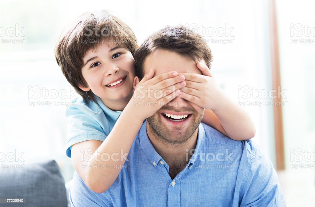 Boy covering father's eyes stock photo