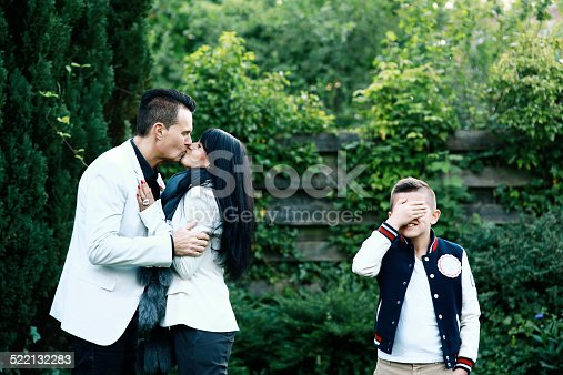 istock Boy Covers His Eyes as Parents Kiss 522132283