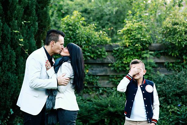 ragazzo copre i suoi occhi come genitori baciare - kids kiss embarrassed foto e immagini stock