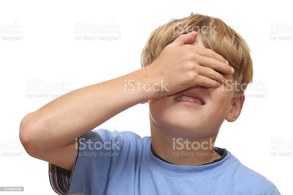 Boy covers his eyes stock photo