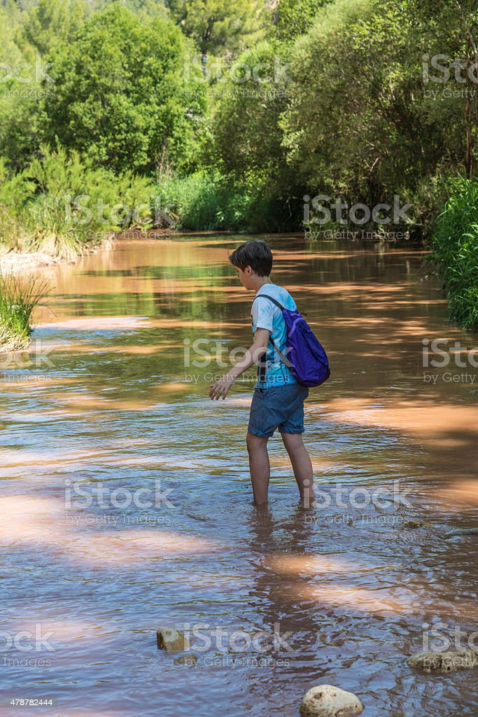 Boy crossing a river stock photo