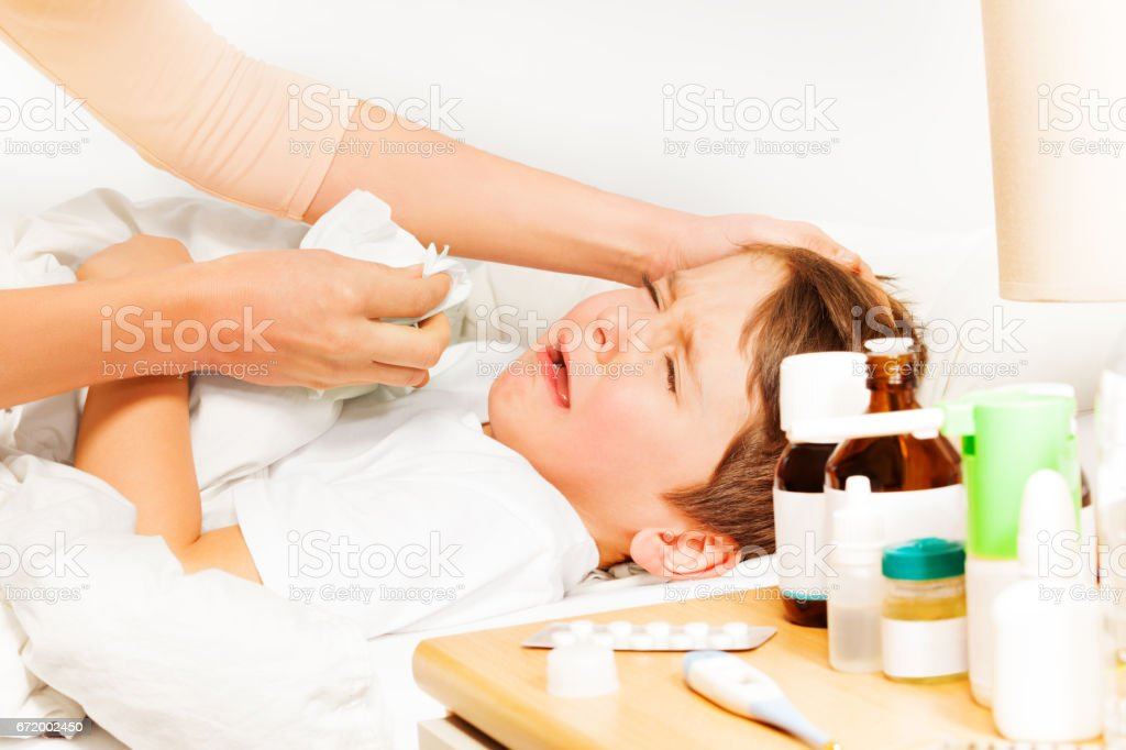 Boy crying while mother helping to blow his nose stock photo