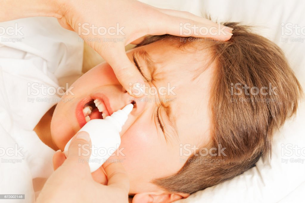 Boy crying while mother spraying him nasal spray stock photo